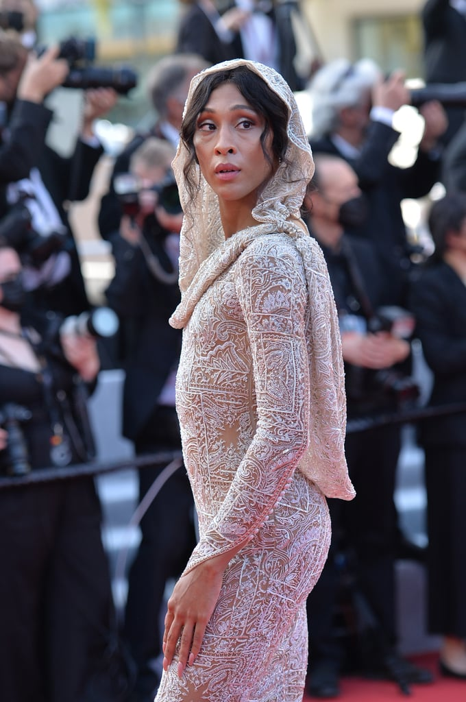 """Mj Rodriguez has made her Cannes debut, and she certainly dressed for the momentous occasion. The actress and Pose star attended the esteemed film festival's opening ceremony on July 6 wearing a custom design by Etro. Mj described the experience as a """"dream"""" on Instagram. She added, """"It was a true fairytale!""""  Entirely embroidered in crystals and glass beads, Mj's glamorous gown also featured a sexy open-back silhouette, interesting glove sleeves, and a draped hood, which overall offered a very coy look. Mj kept the accessories simple, opting for classic drop earrings and a sapphire ring. Her sultry hair and makeup, meanwhile, were inspired by Mozart's famous """"Queen of the Night"""" aria. She said on Instagram Stories, """"I wanted to be clean, pristine, but also very forward and sharp and edgy."""" Take a closer look at Mj's striking red carpet appearance ahead.      Related:                                                                                                           Bella Hadid Kicks Off the Cannes Glamour in a Dress With a Heck of a Train"""