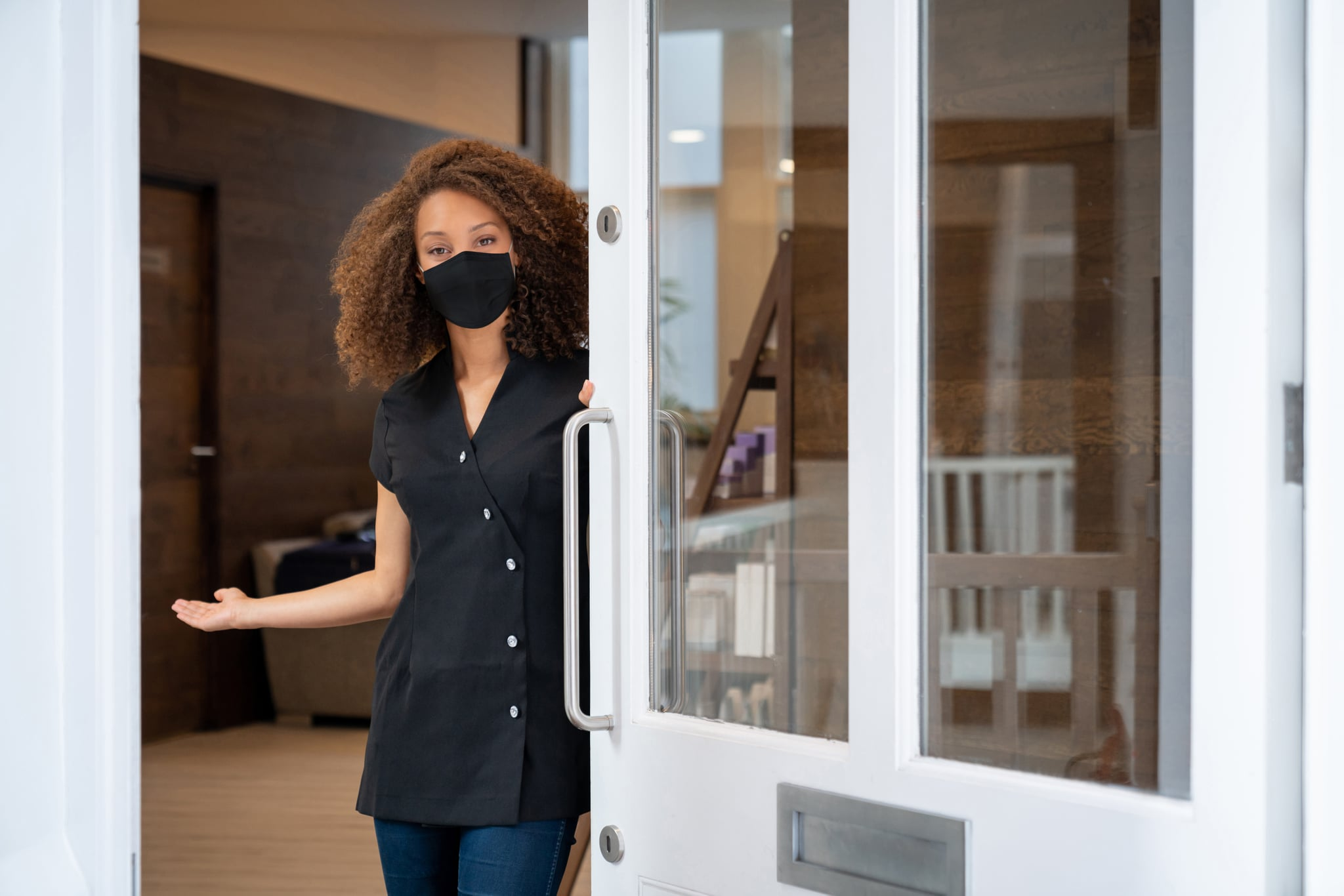 Business owner opening the door of her spa wearing a facemask to avoid the coronavirus a?? pandemic lifestyle concepts