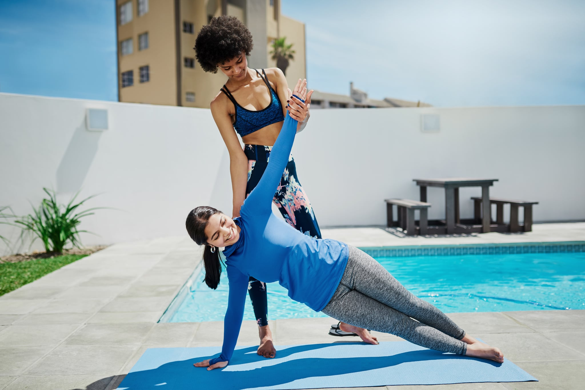 Shot of a young woman being assisted by a yoga instructor in a garden