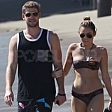 Miley and Liam walked arm-in-arm on the beach.