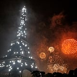 Red and orange fireworks burst beside the Eiffel Tower for Bastille Day.
