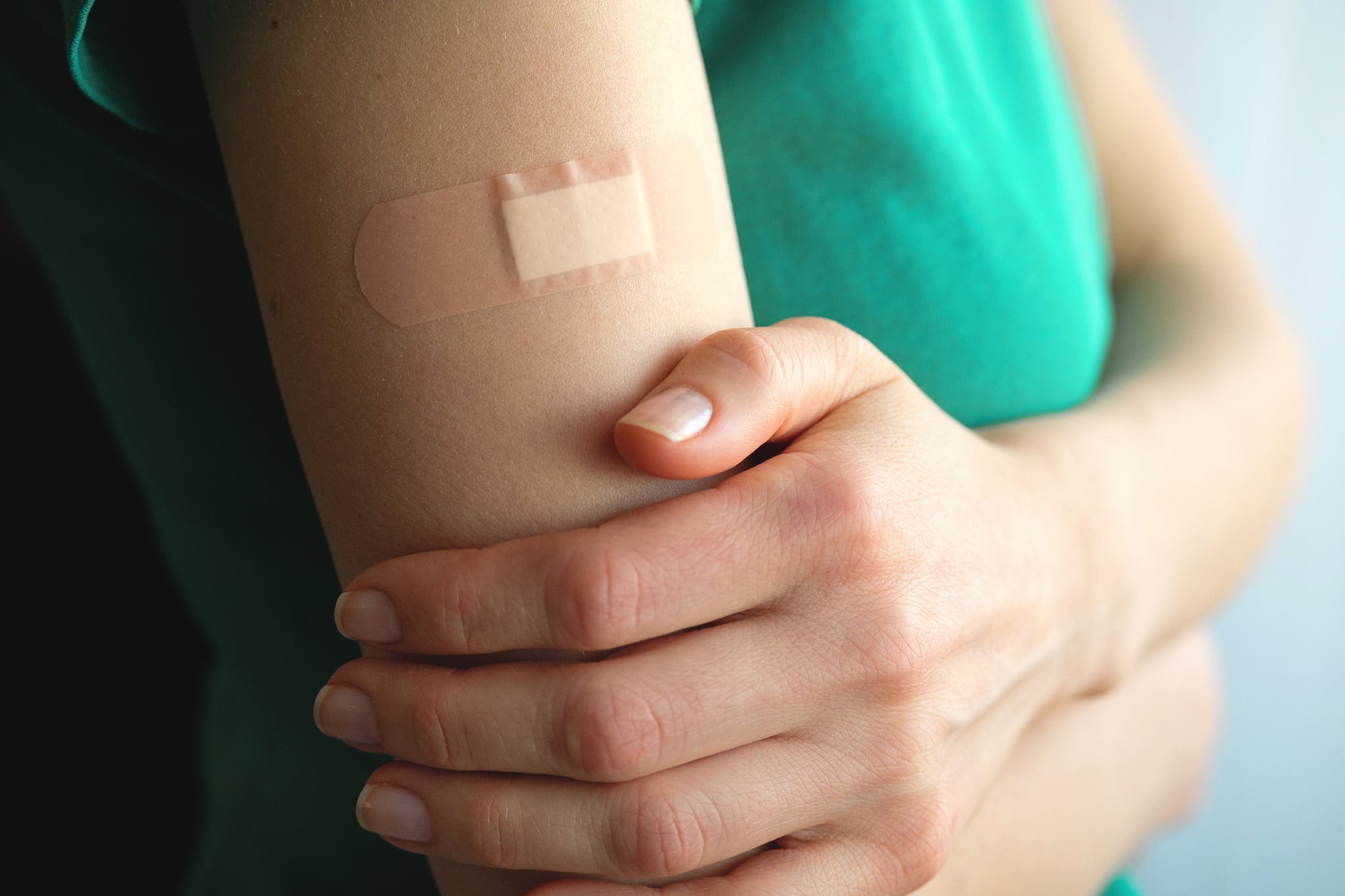 A girl or young woman holds her hand, which is covered with a patch or adhesive bandage after vaccination or injection of medication. The concept of medicine and health care, vaccination and treatment of diseases. First aid.