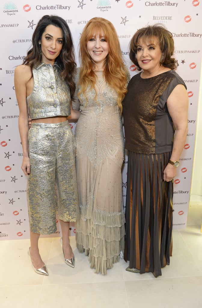 Amal Clooney brought her mother, Baria Alamuddin, to the launch of makeup artist Charlotte Tilbury's new flagship beauty boutique in Covent Garden on Thursday. The event, called Charlotte's Naughty Christmas Party, also brought out Salma Hayek, Kate Bosworth, Kate Moss's younger sister, Lottie, and Charlotte's own stunning mother, Patsy. Amal showed off her standout style in a metallic crop top with matching trousers and posed for photos with her look-alike mum during the soirée.  We last got a glimpse of Amal in October when she supported her husband, George, at the premiere of his film Our Brand Is Crisis in LA. Not long after their red carpet appearance, news broke that the couple had expanded their family; George and Amal adopted a rescue dog named Millie from the San Gabriel Valley Humane Society in California. Keep reading to see photos from Amal's night out, then see all the times she and George looked madly in love.