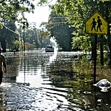 A man in Gonzales, LA walks down his flooded street to assess his home's damage.