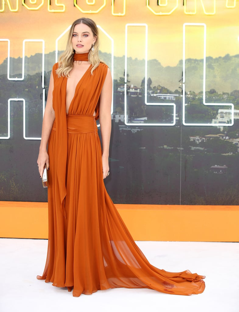 Yes, Brad Pitt and Leonardo DiCaprio were at the Once Upon a Time in Hollywood UK premiere, but it was Margot Robbie who brought the heat in a fiery Oscar de la Renta gown. As the rest of us slowly start to face the end of Summer, the 29-year-old actress jumped right into Fall colours with a purely autumnal colour palette on the red carpet — not that you can confuse her outfit with cosy sweaters and boots.  Margot's burnt-orange gown, from the Fall/Winter 2019 collection, featured a plunging neckline and gaping cutouts along the upper sides, with a wraparound scarf detailing. Now, that's one way to combine Summer and Fall trends into one. The skin-baring top came with a flowing skirt and train, which gave Margot a goddess-like appearance as she posed for photos. She completed the gorgeous outfit with dangling earrings, a massive gold ring, a reflective Edie Parker clutch, and metallic heels.  Costars Brad and Leo complemented Margot's ensemble well in their dapper suits. Brad opted for a navy blue coat and trousers with a black sweater underneath, while Leo kept things classic in a charcoal set and sunglasses. They make a suave trio, indeed! Ahead, see every angle of Margot's evening out and zoom in for a closer look at her incredible matching makeup.