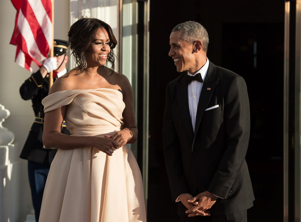 Leave it to Barack and Michelle Obama to keep the sweet moments coming. On Friday night, the couple hosted the prime ministers of Denmark, Iceland, Norway, and Sweden, as well as the president of Finland, for the Nordic state dinner in Washington DC. Both Michelle and Barack looked happy and at ease as they served up some serious glamour and flashed big smiles while greeting their guests. At one point, the first lady was even spotted wiping off a speck from the president's chin. The fete boasted a guest list that included stars like Miranda Kerr, Tracee Ellis Ross, new couple Bellamy Young and Ed Weeks, and Demi Lovato, who took the stage for a performance. Read on for more photos, and then take a look at all of Michelle's celebrity encounters.