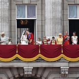 The royal wedding family stands on the balcony with the kissing newlyweds.