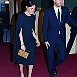 For Queen Elizabeth's 92nd birthday celebrations, Meghan stunned in a sleek and sophisticated navy blue cape dress by Stella McCartney. She accessorised it with navy suede Manolo Blahnik pumps, Isabel Marant gold hoop earrings, and her Naeem Khan zodiac evening bag in Leo.