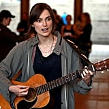Keira Knightley strums a guitar on set.