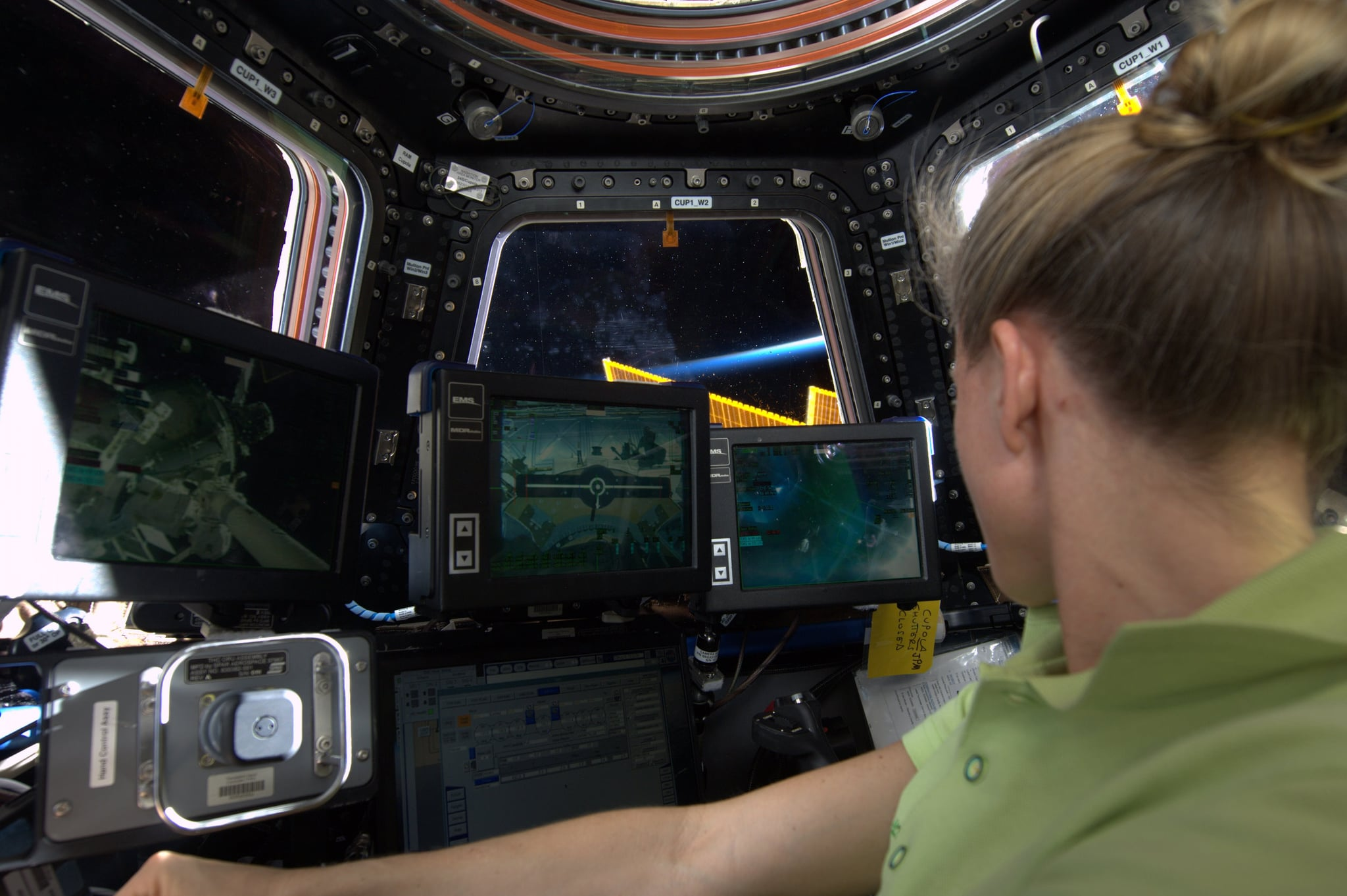 """""""At the Robotics Work Station in the Cupola. This is where we'll be to capture #HTV4 cargo vehicle with #Canadarm2 on Friday, August 9. My incentive: garlic paste and a care package from home! KN from space."""" Source: Pinterest user Karen Nyberg"""