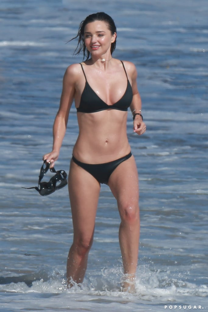 """Miranda Kerr was on the beach in Malibu, CA, on Monday for a swimwear photo shoot. The Aussie model sported multiple suits for her day on the water — including a black bikini, floral two-piece, and sleek one-piece — and playfully posed in the ocean with a group of hot surfers. Miranda's beach day came just a day before her boyfriend of a year, Snapchat founder Evan Spiegel, asked her to marry him. Us Weekly reported earlier this month that the couple is """"completely smitten"""" and that Evan was """"starting to look at rings."""" A source added that the pair will have an """"extravagant wedding, in true Evan style."""" He definitely did a great job with that rock!"""