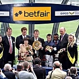 Prince Harry presents a horse racing medal.