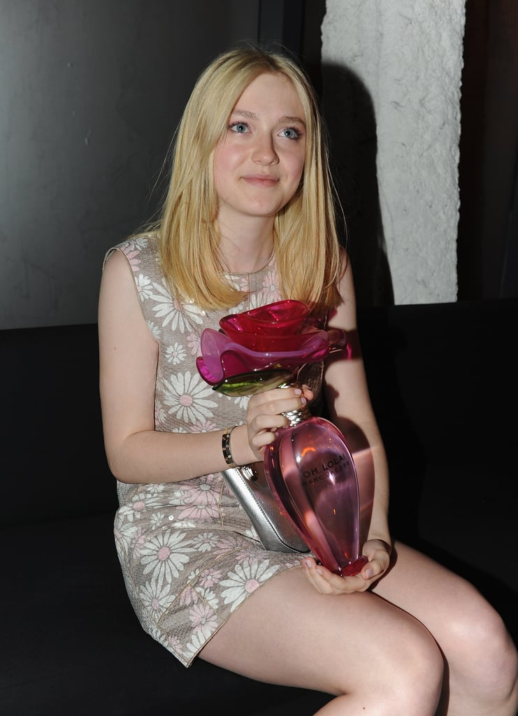 Dakota held onto a large perfume bottle after the show.