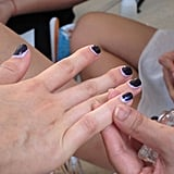 A nail tech applies a top coat to seal the manicure.