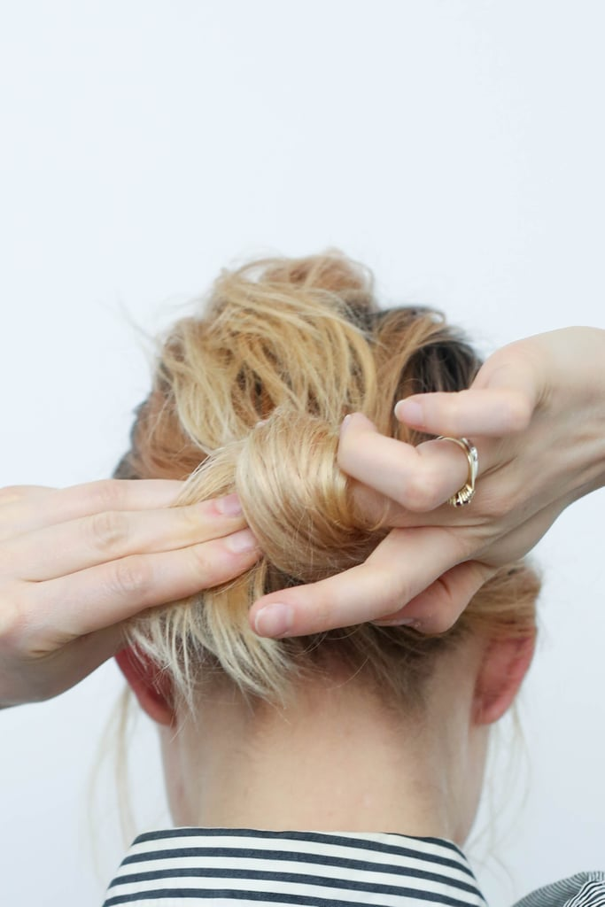 With just your hands, gently gather back the rest of your hair into a low ponytail. Using a finger on your right hand as an anchor, pull the end of the tail taut with the left to your left side. With the anchored right finger, twist your hair clockwise toward the back of your head twice and lay against the back of your head. While twisting, be sure to continue to hold the ends of your hair securely with the left hand until they are all wrapped up in the twist.