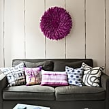 To maximise space, Ali and Lindsay choose side and coffee tables that double as stools for additional seating. To add personality, they hung a magenta juju (African feather headdress) above the sofa. Photo by  Matthew Williams via LABLstudio