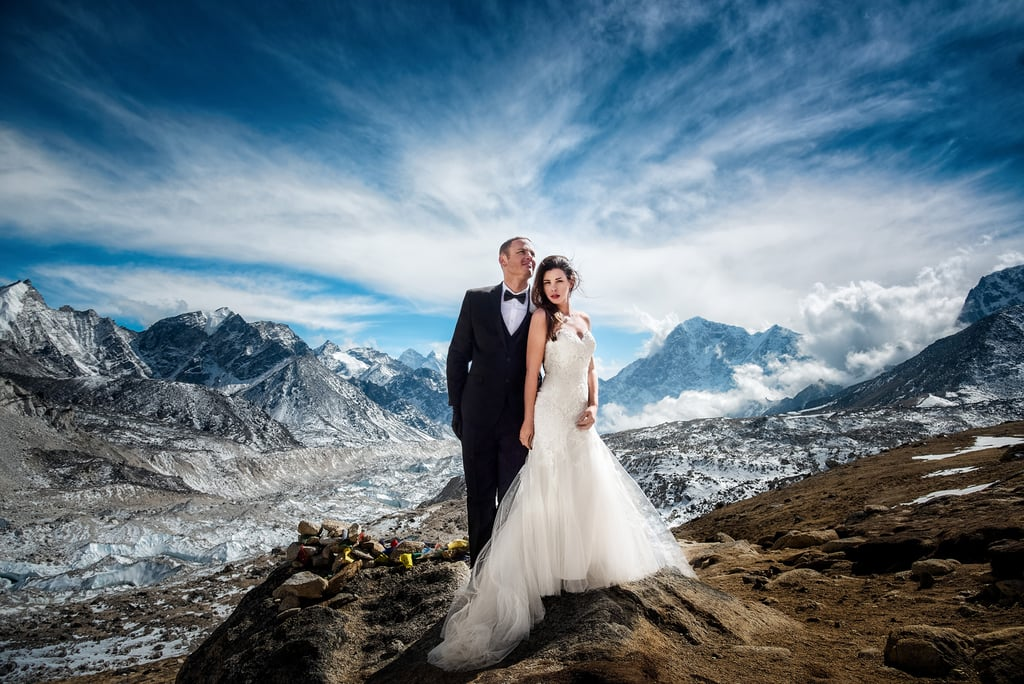 """Some couples opt for a casual wedding with no frills and little stress. Some couples don't. James and Ashley decided that instead of your average nuptials, they'd do something a little more adventurous. They were married at a Mt. Everest base camp and became the first couple to exchange vows in an actual wedding dress and tuxedo on the mountain. """"We trained for the year and planned to be on the mountain for two to three weeks in order to acclimatize our way up to base camp so James and Ashley can get married and get a few photos,"""" said Charleton Churchill, the adventure photographer who shot the breathtaking photos. """"I had attempted base camp with another in 2015, but the devastating earthquake of Nepal including the massive avalanche that swept EBC turned everyone around off the mountain. I wasn't sure if I would find another couple to get married on Everest anytime soon,"""" he added. James and Ashley, however, were ready to try it. The couple reached out to Churchill and were prepared to do what it took to hike to the base camp and say their """"I dos"""" against the backdrop of the tallest mountain in the world. If there's any way to test the strength of a relationship, we'd bet it's by forging upward through snow and ice, facing high altitudes, physical stress, and unpredictable weather — together. """"There's no glory without suffering."""" """"Now saying this was an epic and amazing trip is true, but I would be remiss if I didn't share it came with some suffering, doubt, fear, anxiety, and physical pain. Often times when striving for something great, there's usually a cost. There's no glory without suffering. We worked hard for these images with much less time to photograph a short wedding than we planned. It started snowing hard a few days into the journey. According to our Sherpa guide, it dumped more snow on us than it had all winter. The temperatures ranged from -8 degrees to 10 degrees Fahrenheit from 14,000 ft. camp and above,"""" Churchill said on his site. James also had """