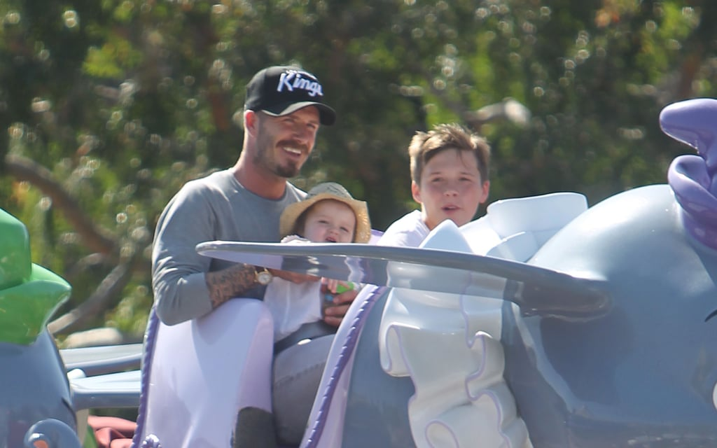 In June, Harper sat on dad David Beckham's lap with brother Brooklyn next to them on a ride at Disneyland.