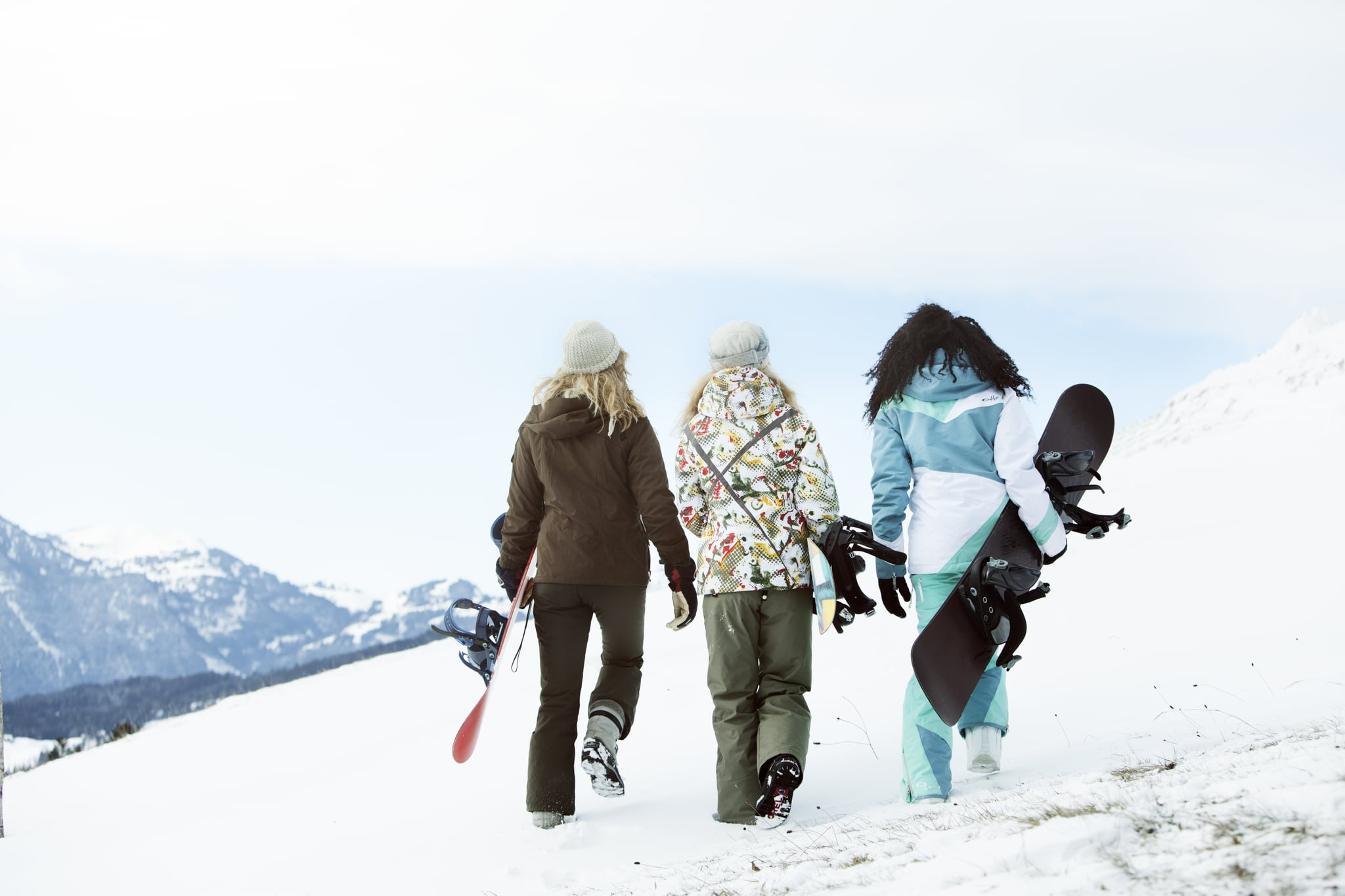 3 young women with snowboards, rear view,  on winter holiday in switzerland,