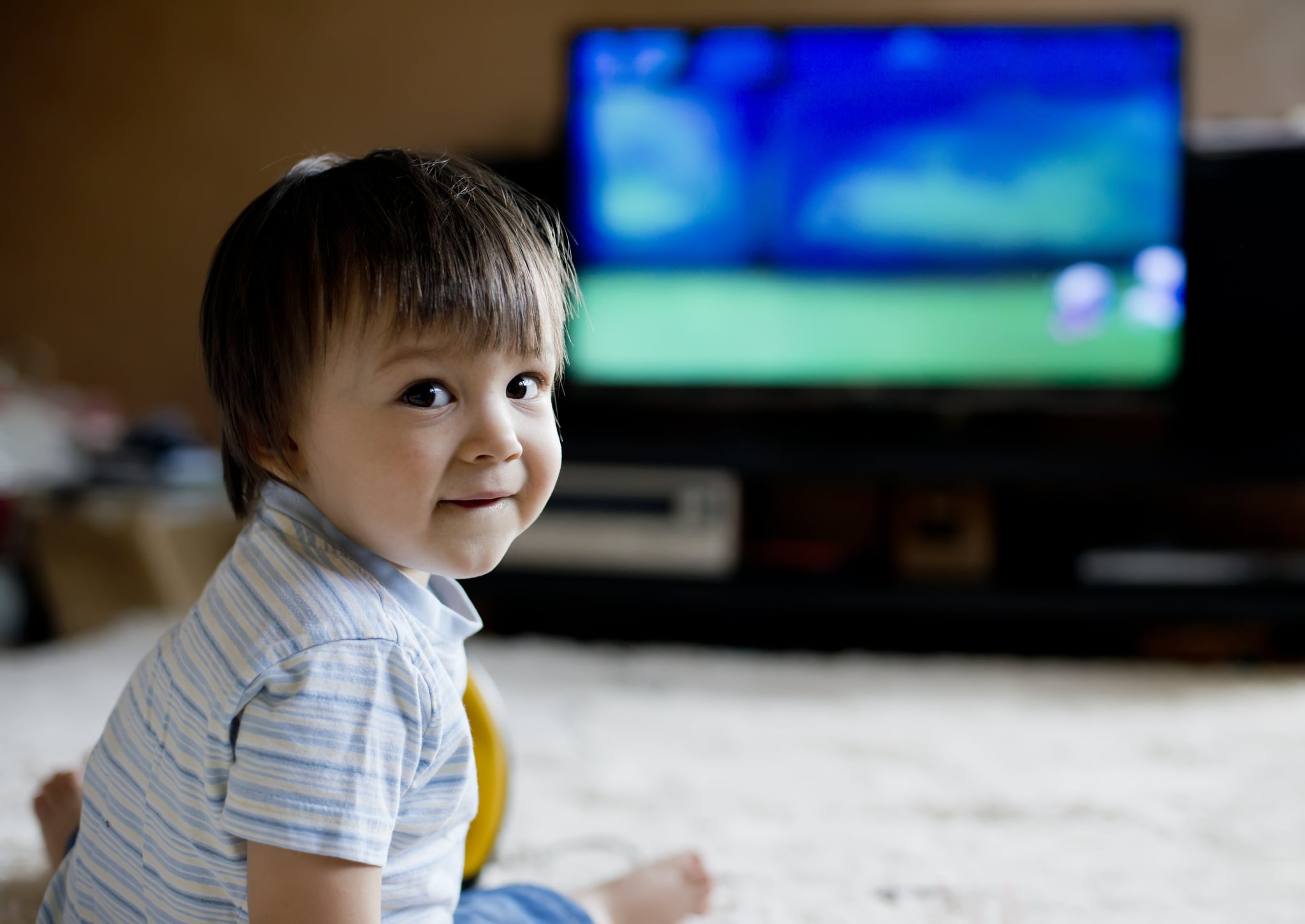 Little boy sitting on carpet and looking TV