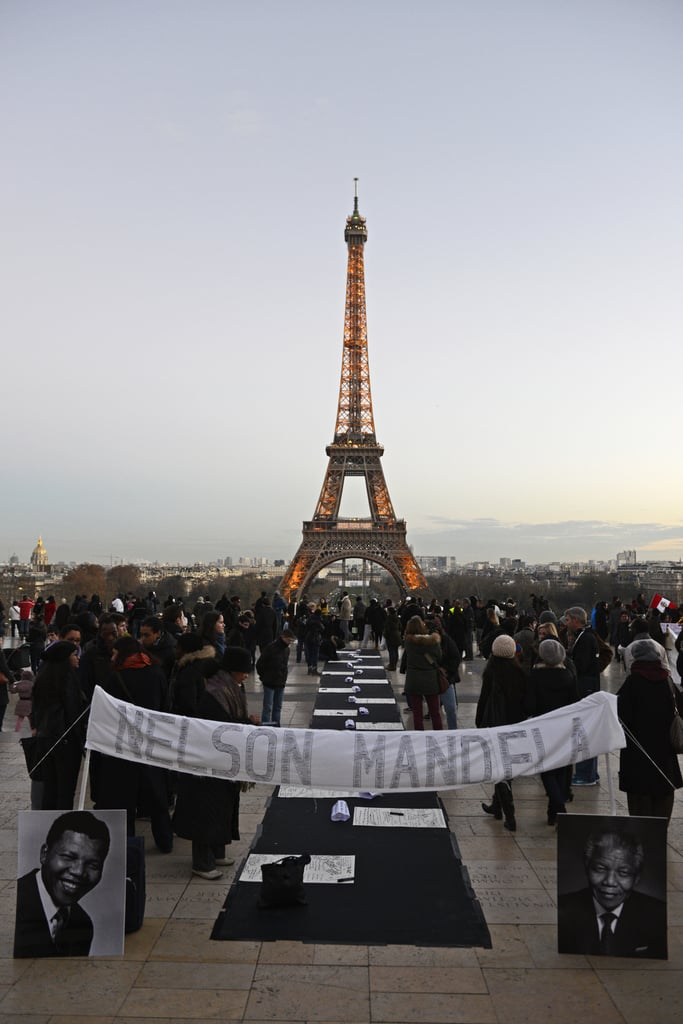 Signs, pictures, and candles covered Human Rights Square in Paris, France.