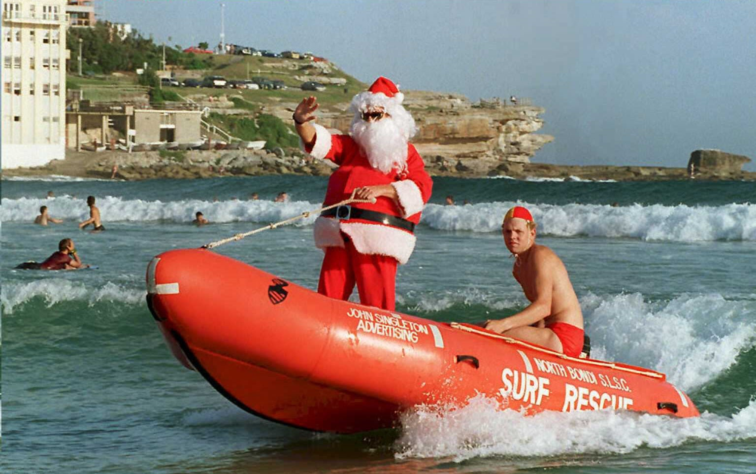 SYDNEY, AUSTRALIA - DECEMBER 22:  Santa Claus arrives aboard a surf rescue inflatable at Sydney's Bondi Beach 22 December where the tradition of volunteer surf lifesaving began in 1903. Sydneysiders celebrate the Christmas season on the harbour and ocean beaches to avoid the summer heatwaves. (Colour key: Santa wears red)  (Photo credit should read TORSTEN BLACKWOOD/AFP/Getty Images)
