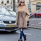 Olivia added her Max Mara coat to distressed jeans and YSL booties while running around PFW.
