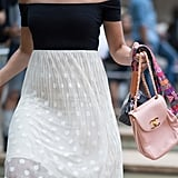 A camera with a quirky strap looks so much more chic fronted by a powder-pink Chanel handbag.