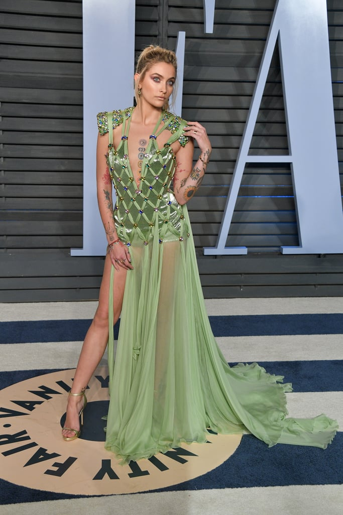 "Paris Jackson is glowing! The 19-year-old model and daughter of the late Michael Jackson left her wand and fairy wings at home, but she still managed to shine bright at the 2018 Vanity Fair Oscars afterparty. In a stunning Versace gown, Paris transformed into a sexy Tinker Bell for Sunday night's events, even sharing in her Instagram comments that she was going for the look of the Peter Pan pixie character. The colourful embellished gown was the ideal shape to flaunt each of her vibrant tattoos. What may look like a simple, nostalgic tribute to the Disney days could actually be an outfit created in honour of Michael. In a 2017 interview, Paris told Rolling Stone that her father would call her Tinker Bell, as his only daughter. With her father's obsession with Neverland and actually seeing himself as Peter Pan, we can't help but connect this sweet moment to her Oscars outfit. Paris also has ""faith, trust and pixie dust"" tattooed on her collarbone. Read on to see Paris's magical outfit from all angles.      Related:                                                                                                           Wow! You'll Forget About the Oscars Red Carpet When You See These Glam Afterparty Looks"