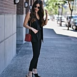 Mimic a pantsuit by pairing slim trousers or jeans with a matching vest, then add a bright bag to add interest.