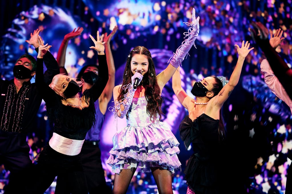 """Olivia Rodrigo has a thing for Y2K trends. In addition to wearing vintage designs from the millennial decade, the singer has been testing out its hair trends, too. While performing """"Good 4 U"""" at the 2021 MTV Video Music Awards, Rodrigo wore her waist-length hair in loose waves with face-framing baby braids and butterfly clips sprinkled throughout. Earlier in the night, Rodrigo actually wore statement-making butterfly earrings with her vintage Versace gown.  For Rodrigo's red carpet arrival, hairstylist Clayton Hawkins kept things sleek and simple, prepping her hair with Matrix's Total Results A Curl Can Dream Lightweight Oil, and creating waves with a one-inch curling iron. Rodrigo's hair was then parted in the middle and tucked behind her ears. For the prom-aesthetic performance, Hawkins added in the braids and vintage butterfly clips, locking in the look with the Matrix Total Results High Amplify Flexible Hold Hairspray. See the sweet hairstyle switch-up ahead.      Related:                                                                                                           The MTV VMAs Red Carpet Is So Upbeat, the Fashion Alone Will Make You Get Up and Dance"""