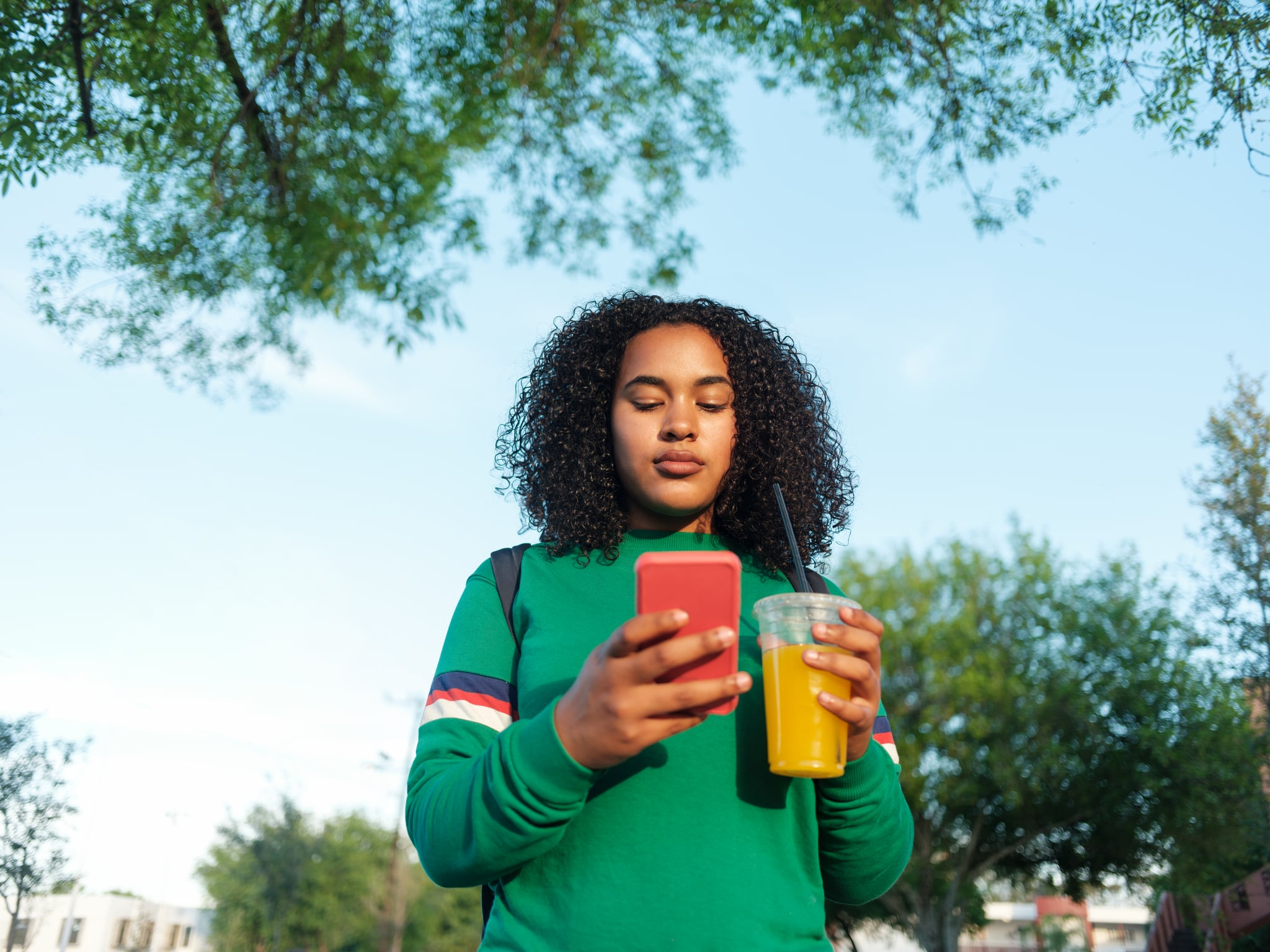 A college girl holding a healthy drink and texting outdoors.