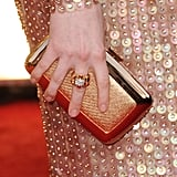 Anne Hathaway's Roger Vivier clutch and Van Cleef & Arpels ring.