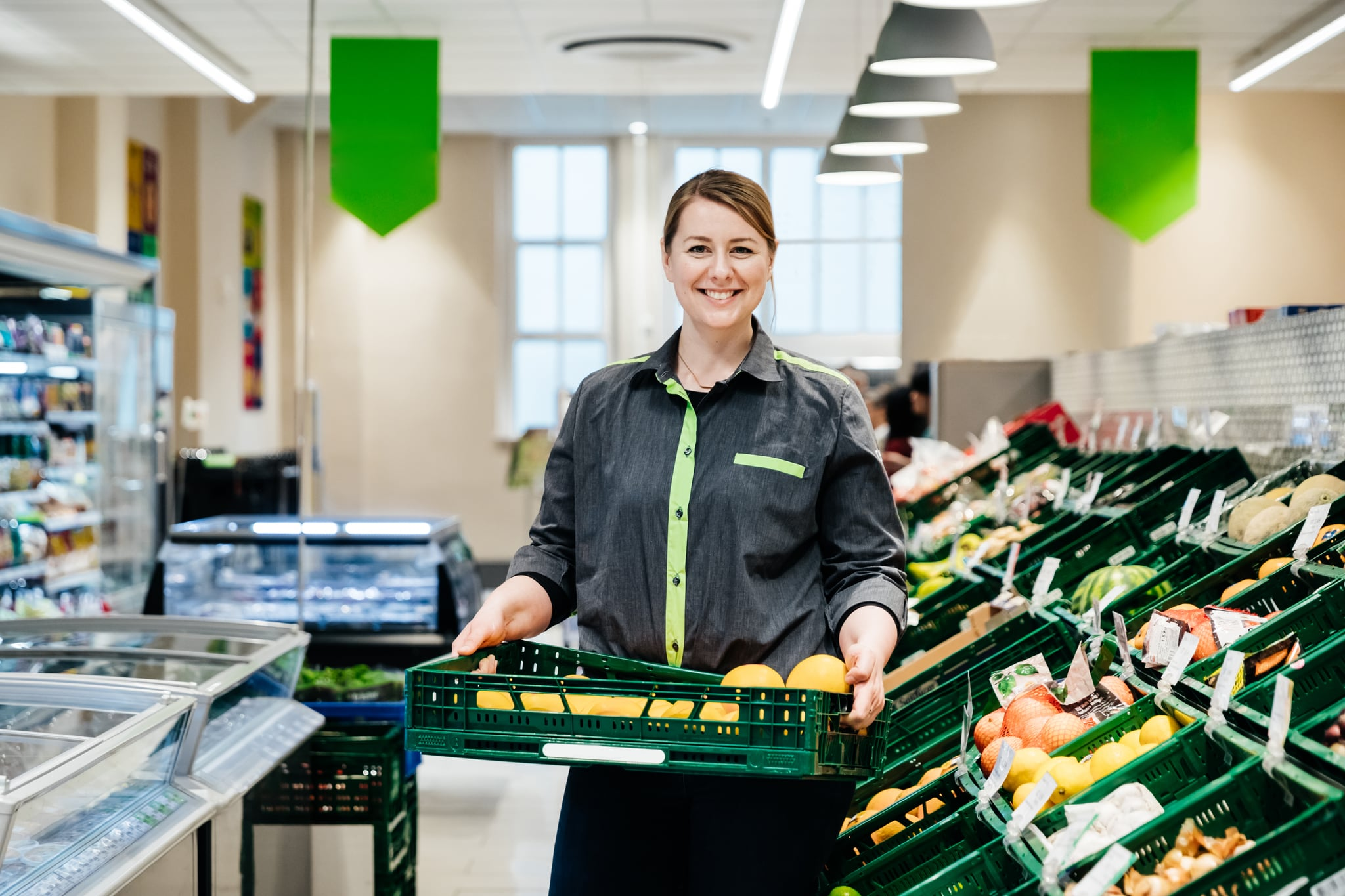 A portrait of a supermarket employee smiling and holding a crate of fruit.