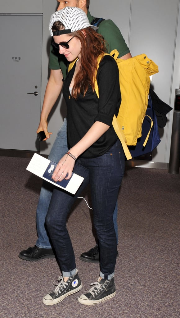 Kristen Stewart wore a backwards ball cap arriving in Japan.