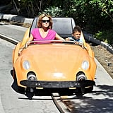Heidi Klum and Henry driving cars at Disneyland.