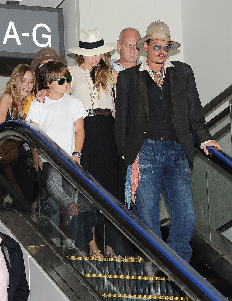 Amber Heard and Johnny Depp both wore hats through the airport.