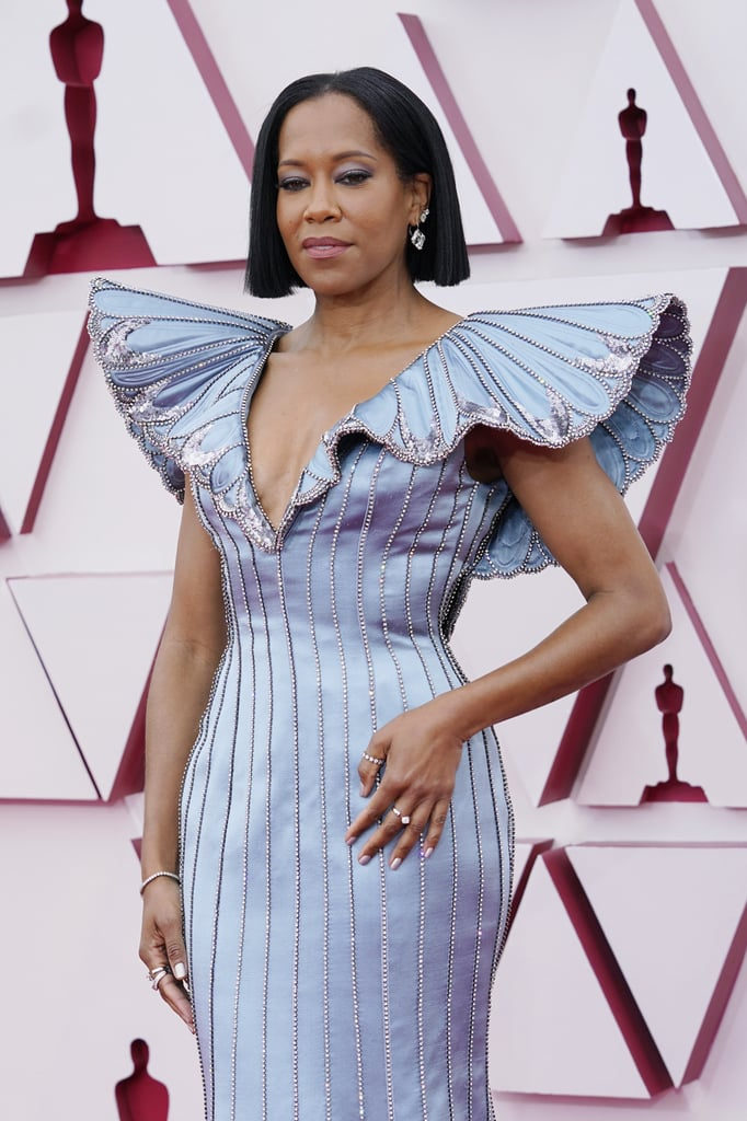 """When it comes to the red carpet, there's everybody else, and then there's Regina King. The actress and director of One Night in Miami proved that she's the indisputable queen of awards shows when she rolled up to this year's Oscars in custom Louis Vuitton looking like an ethereal butterfly.  In a pretty pastel blue hue with pronounced sleeves and a formfitting bodice, the floor-length gown is precisely the kind of look that will prompt all of Twitter to declare: """"Everybody else can go home."""" King's regal stance certainly doesn't hurt, either. Regina King . . . or Regina Queen? Check out more photos of King's dress ahead."""