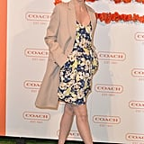 January Jones paired a blue-and-yellow floral dress with a cool camel overcoat and Coach's Terri woven-heel sandals.