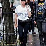 Wearing Paige jeans, a Saint Laurent tee, Converse sneakers, and Karen Walker sunglasses.