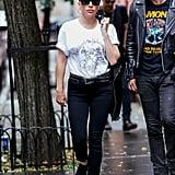 Wearing Paige jeans, a Saint Laurent tee, Converse sneakers, and Karen Walker sunglasses.