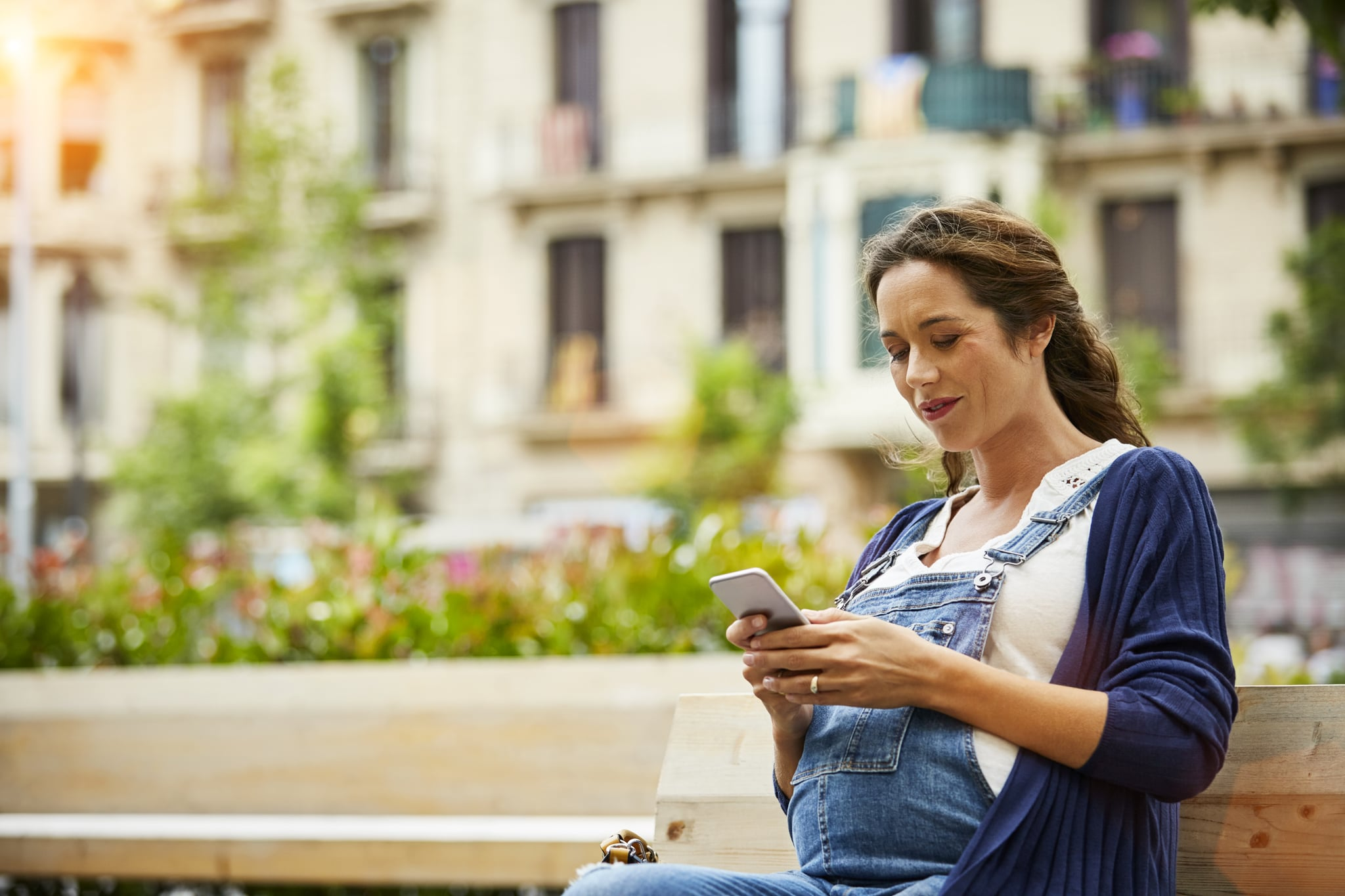 Pregnant woman text messaging while sitting on bench
