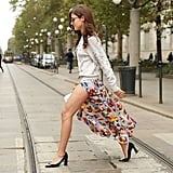 Eleonora Carisi showed off her gams in a colorful printed skirt with a dangerously high slit.