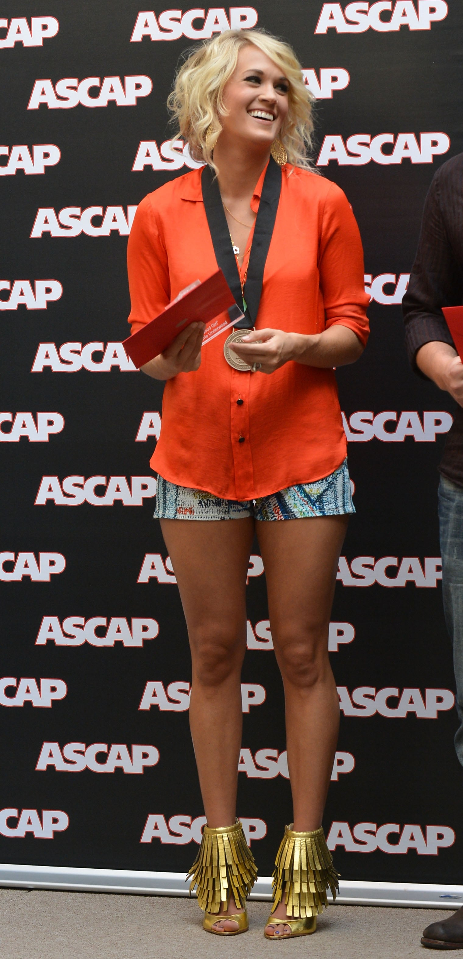 Proving she isn't afraid of a little lot of color, Carrie wowed in an electrifying blouse, tropical-print Rag & Bone shorts, and mirrored metallic sandals in August 2012.