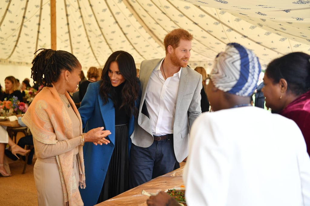 Though Meghan Markle's first official solo royal engagement isn't until Sept. 25, that doesn't mean she's not been keeping busy. On Thursday, the Duchess of Sussex invited women from the Hubb Community Kitchen in West London to join her at Kensington Palace to cook dishes from Together: Our Community Cookbook, the book that Meghan is supporting as one of her first projects as a member of the royal family. Meghan wrote the foreword for the charity book, which contains recipes from members of the community in West London that came together following the devastating Grenfell Tower fire. Dressed in a black turtleneck dress and stylish blue overcoat, Meghan was joined by Prince Harry and her mom, Doria Ragland, whom we last saw front and center at the royal wedding. Their mother-daughter bond was on show once again as Meghan introduced Doria to the special guests who helped create the cookbook.  Meghan's next appearance will be on Sept. 24, when she and Prince Harry attend the Coach Core Awards. The following day, she'll step out on solo official duties for the first time when she attends the opening of Oceania, a new exhibition at London's Royal Academy of Arts.