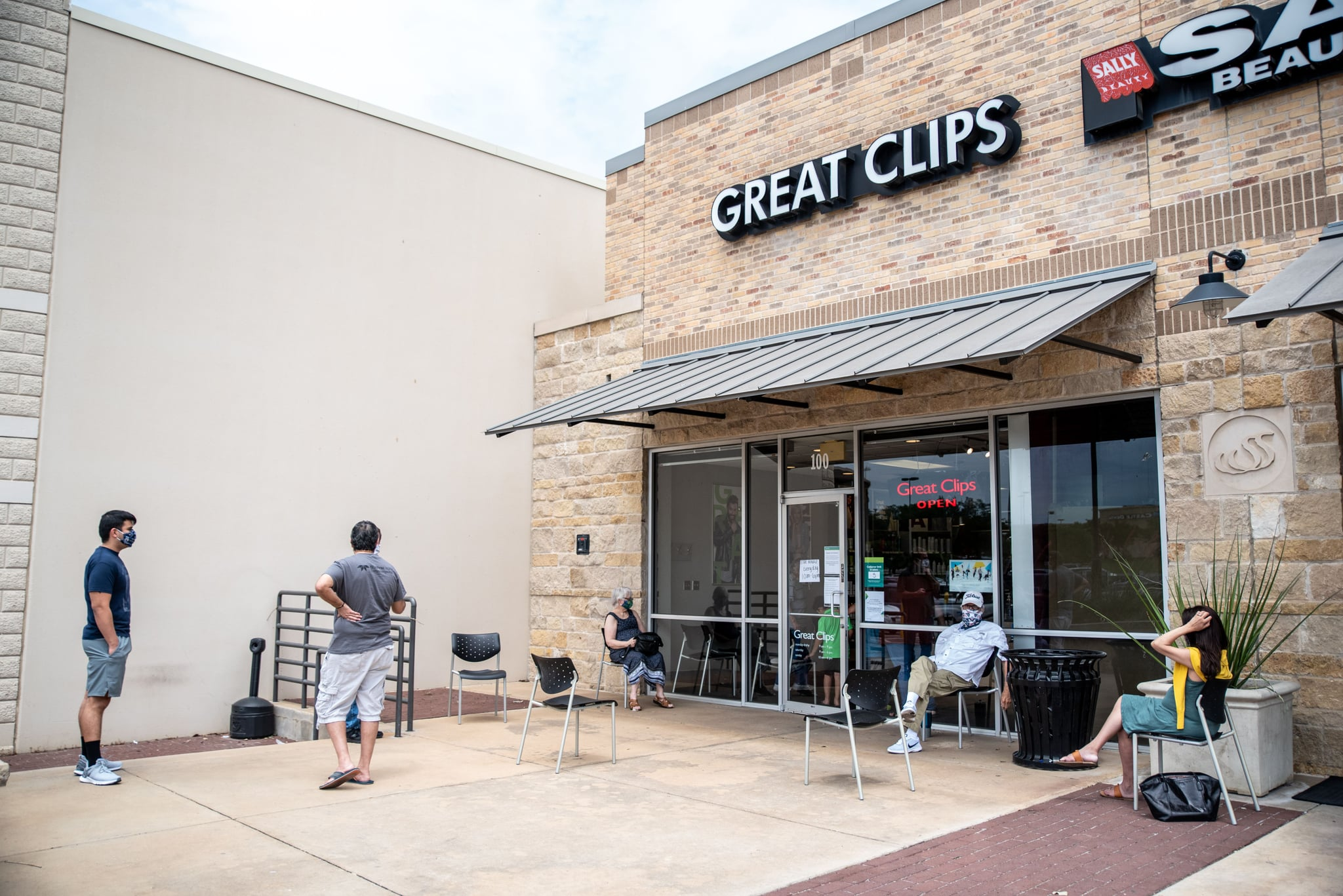 People wait for their haircuts outside Great Clips amid the coronavirus pandemic in Round Rock, Texas on May 8, 2020 following a slow reopening of the Texas economy. - A Texas hairdresser was sentenced to seven days in jail for keeping her salon open in violation of lockdown orders to slow the spread of the coronavirus, a move that state legislators decried on May 6, 2020 as