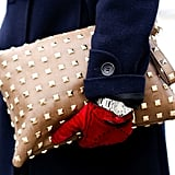 An oversize studded camel clutch gave a tough touch to a pair of chic red gloves and a navy coat.