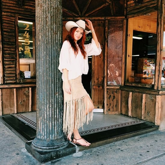A cowboy hat and fringe give off strong Western vibes, sure, but you can avoid coming off as too costumey with simple sandals and an oversize blouse instead of, say, cowboy boots or a vest. Source: Instagram user seaofshoes