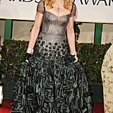 Madonna wore a sequined silver and green bodice gown by Reem Acra, complete with fingerless gloves. Since the dress spoke for itself, she kept the rest of her look minimal, donning her trademark cross necklace.