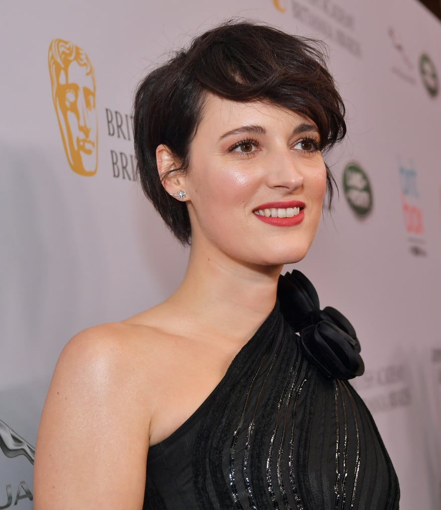 As if we needed another reason to love Phoebe Waller-Bridge (her talent, her humor, her sense of style — the list goes on), the Emmy-Award-winning actress and producer chopped her hair into a shaggy pixie cut that we can't help but love. Waller-Bridge debuted her supershort new 'do while attending the British Academy Britannia Awards in Beverly Hills this past Friday, and she looked like a total rockstar. Arriving in a black one-shoulder Armani jumpsuit, Waller-Bridge paired the outfit with Graziela Gems jewelry and striking red lipstick that Fleabag herself would definitely approve of. Her face-framing new haircut completed the outfit, giving Waller-Bridge an edgy new look that has us tempted to call our hairstylists ASAP. Keep scrolling to take a look at her stylish new haircut from all angles ahead.